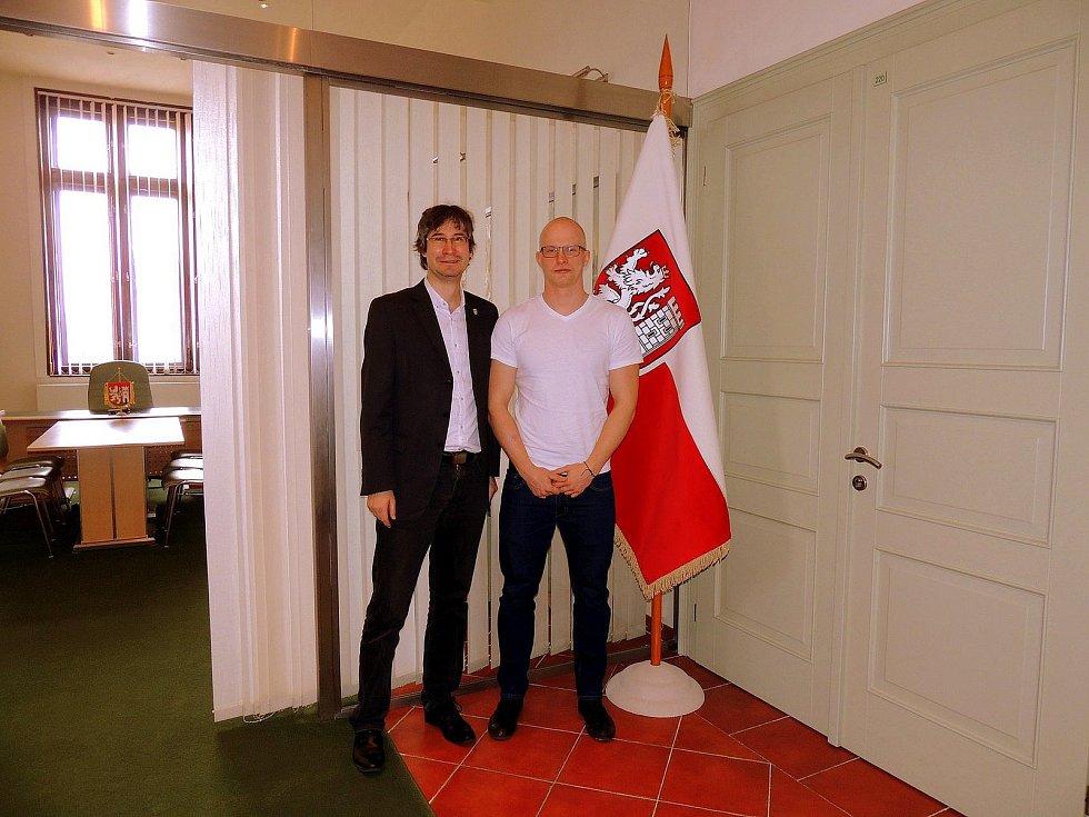 Nymburský bobista Jan Šindlář (bez vlasů) krátce před odletem do Koreje na nymburské radnici se starostou Pavlem Fojtíkem.