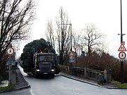 Vánoční strom míří přes kamenný most na náměstí.