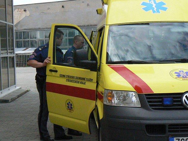 Záchranka za asistence vězeňské stráže převáží muže do vězeňské nemocnice na Pankráci