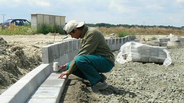 Dělníci připravují okraje budouocí silnice.