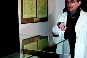 Pracovník Národního archivu se sklání nad vzácnou listinou.