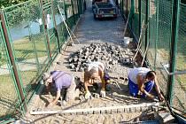 Práce na narovnání dlažby na jezovém mostu začaly.