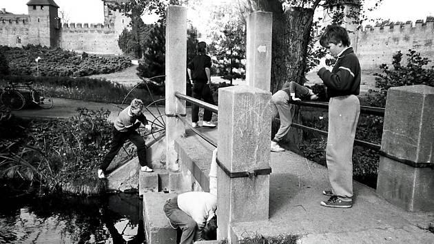 Povedená momentka kluků kolem mostku. Kučeravý chlapec vlevo je sochař Michal Jára.