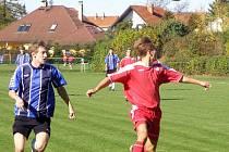 Lyský David Novák (vlevo) se v derby s Ostrou neprosadil, ale zastoupil ho jeho kolega z útoku David Baloun. Před Novákem se snaží odehrát míč Studený (vpravo), vše sleduje Tangl.