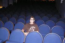 Jára Cimrman Merta ml. sedící, na pódium divadla Na Kovárně hledící.