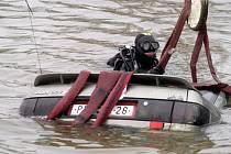Potápěč přivazuje popruhy ke kolům auta