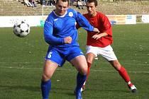 Poděbradský stoper Tomáš Pavel (v červeném) sleduje velkou šanci útočníka Lukáše Došlého