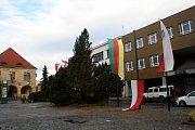 Poničené vlajky na nymburském náměstí