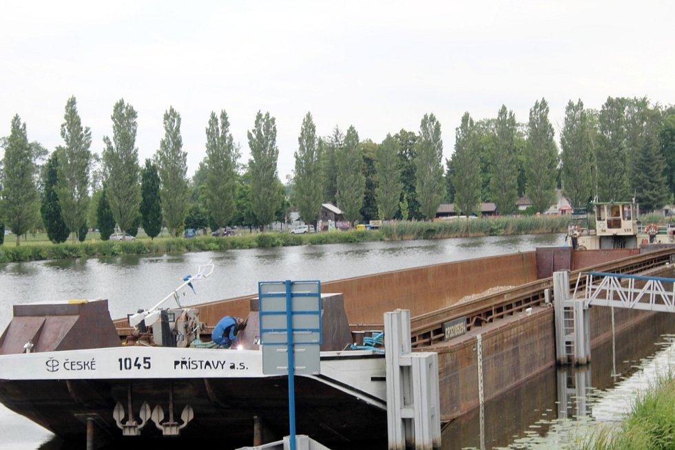 Velká nákladní loď, která v úterý 29. června 2021 převeze střední část lávky nad řeku, už kotví v Nymburce.