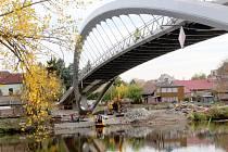 Práce na konci října roku 2021 na stavbě nové lávky přes řeku Labe v Nymburce: úpravy povrchu na samotné lávce, dodělávání příjezdových cest, dláždění přímo pod lávkou na březích.