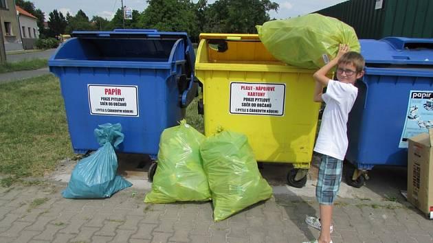 Matěj Havelka vhazuje vytříděný odpad do kontejnerů na adresný pytlový sběr.