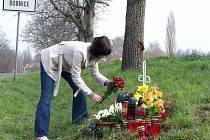 Lidé pokládají k pomníčku květiny a zapalují svíčky