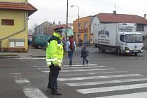 Na křižovatce v Sadské musí ráno strážník pomoci školákům bezpečně přejít. Kruhový objezd jen tak nebude.