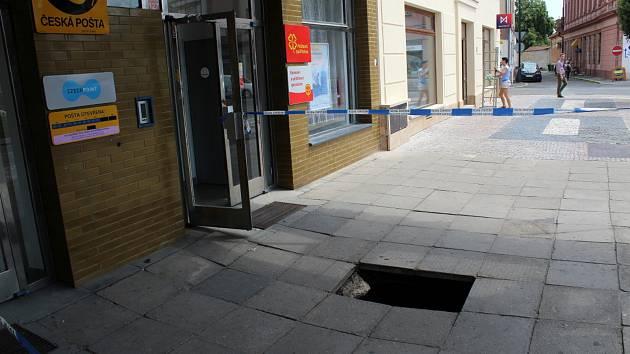 Propad chodníku před vchodem na poštu na náměstí Přemyslovců v Nymburce.
