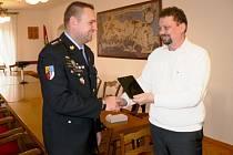 Za policisty přebírá tablet Tomáš Rejman od starosty Jiřího Havelky.
