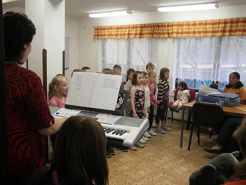 Prvňáčci ze ZŠ Na Valech zazpívali seniorům i barmské rodině v Poděbradech, děti daly barmánkům dárky na přivítanou.