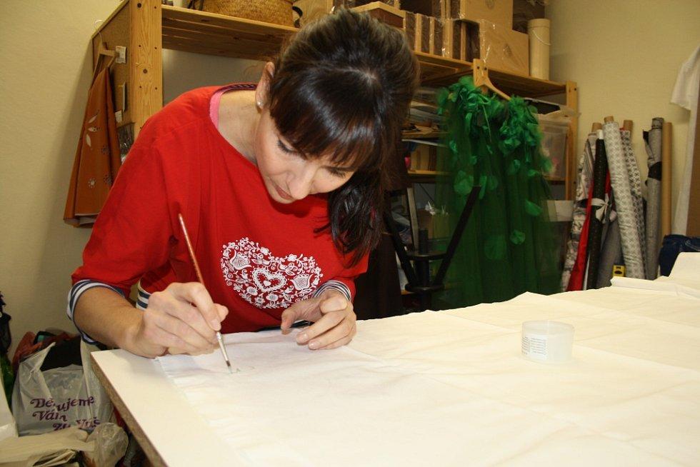 Marie Stará při malování obrázků od dětí z onkologického centra na plátno.