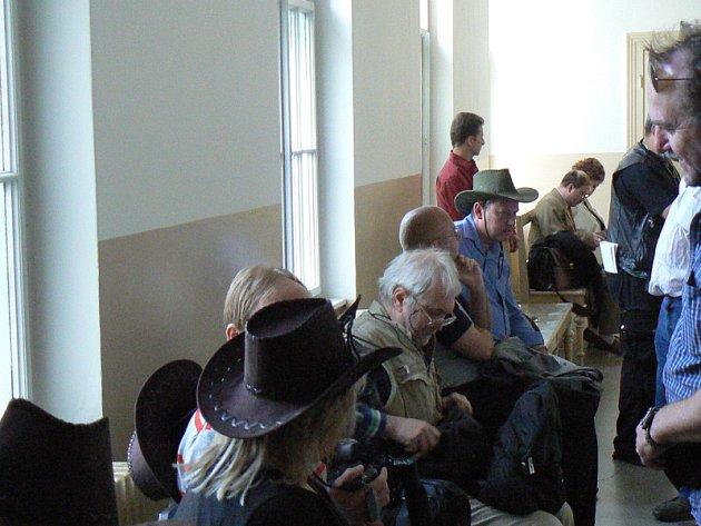 Soudní chodba před hlavním líčení. Jiří Fiala sedící v klobouku a světle modré košili