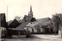 Další historický pohled na domek v historickém centru města. Za ním vykukuje věž kostela svatého Jiljí.