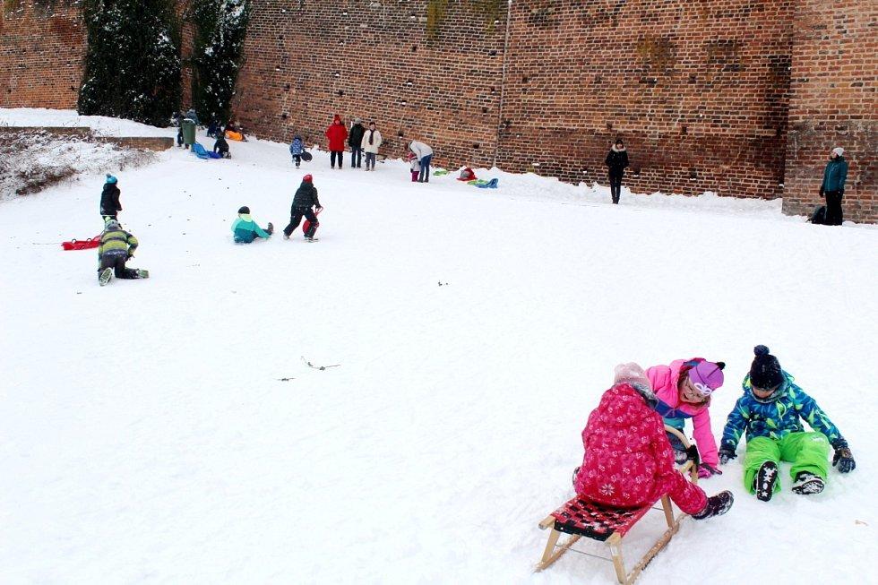 Děti si užívají sníh na několika kopečcích v Nymburce.