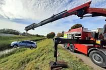 Řidič utopil ve středu 20. října 2021 auto v Mrlině. Hasiči vytahovali škodovku z řeky, při vyproštění použili těžkou techniku.
