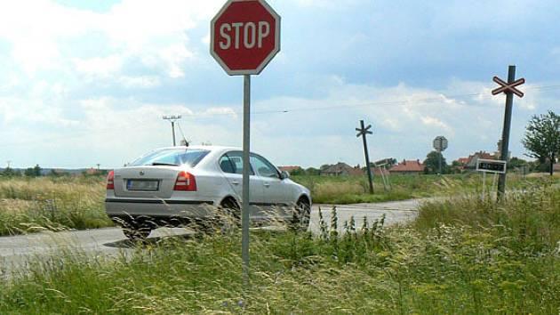 Řada řidičů riskuje střet s motorákem. Alespoň přibrzdí, nebo zastaví zhruba polovina projíždějících, ačkoliv z jedné strany není kvůli vysoké kukuřici na přejezd vůbec vidět.