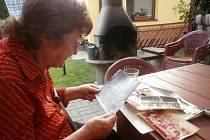 Paní Jaroslava Vendlová vzpomíná nad fotografiemi ze školy.