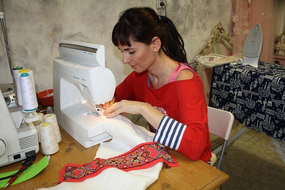 Marie Stará u šicího stroje ve své dílně.