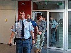 """Obžalovaný Jiří Christ odmítá, že by ubil bezdomovce ve Šternberku. """"Otec to na mě hodil. Vzal si moje boty,"""" bránil se v soudní síni olomouckého krajského soudu. Na snímku vedou obžalovaného do soudní síně."""