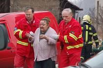 Záchranáři odvádějí k ošetření ženu zraněnou po výbuchu plynu v Dluhonicích