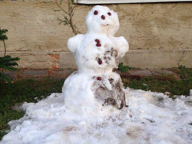Jednoho z posedních sněhuláků, kteří se objevili v ulicích Olomouce po pondělní sněhové nadílce, míjejí lidé v Lidické ulici v Nemilanech. Sluneční paprsky a teploty těsně nad bodem mrazu zimni figury rozpouštěly.