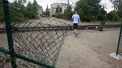 Prostříhaný plot jako alternativa zrušené lávky přes železniční trať.