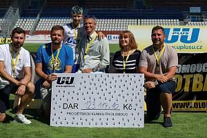 Generální partner Olomoucké fotbalové školy Lukáš Urbanec (uprostřed) symbolicky předal šek přednostce Dětské kliniky FN Olomouc profesorce Dagmar Pospíšilové (druhá zprava).