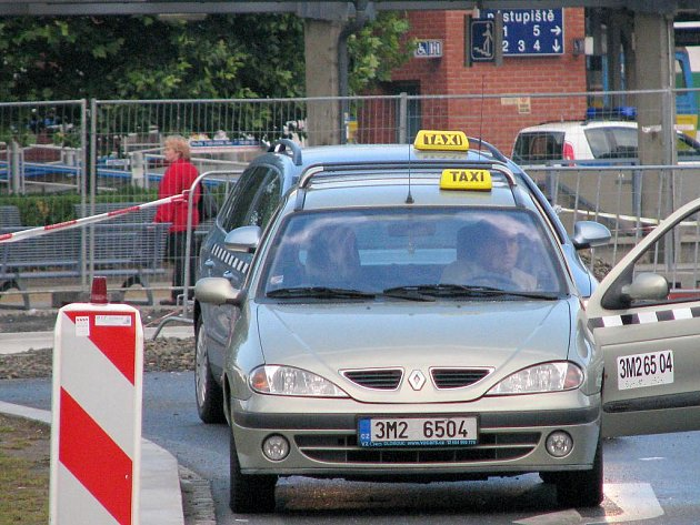Taxi čekající na zákazníky na rozkopaném přednádraží