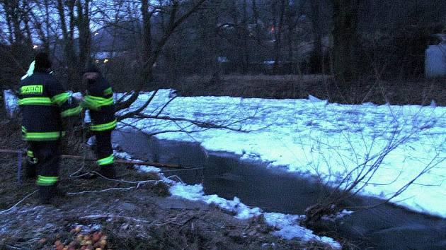Hlídka hasičů u koryta Bystřice plného ledové tříště