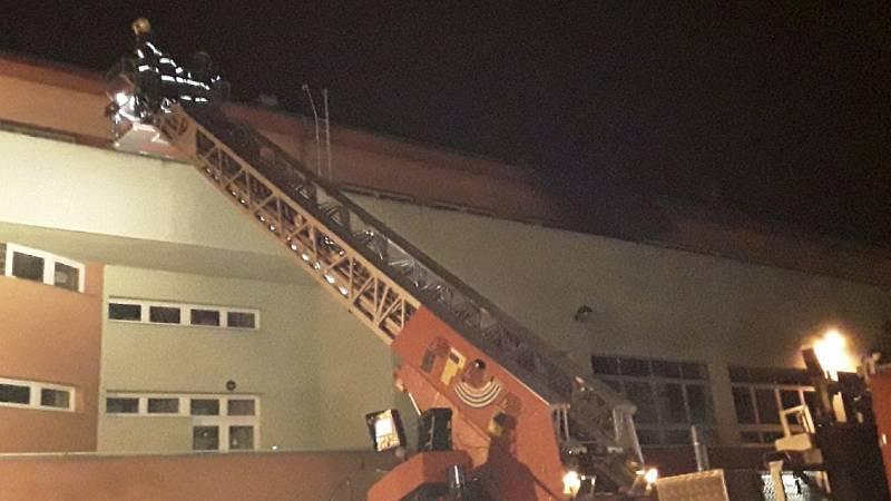 Připevňování střechy na budově přerovské nemocnice. Následky silného větru v Olomouckém kraji v noci z 23. na 24. 2. 2020