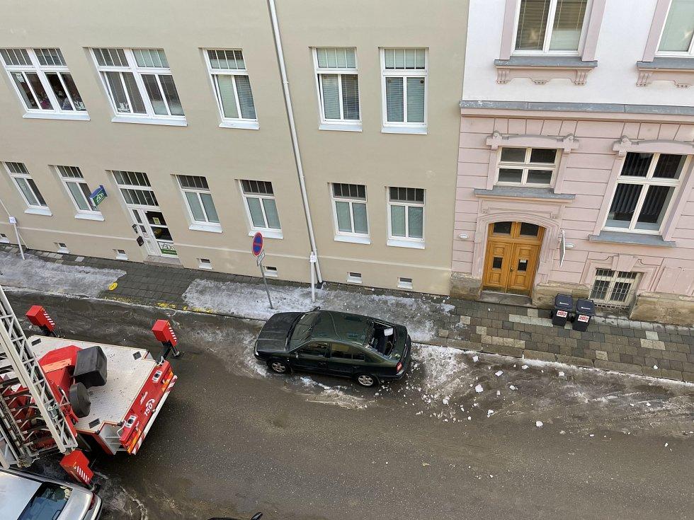 Sněhové převisy ze střech a rampouchy na římsách ohrožují chodce i zaparkovaná auta. Na snímku zásah hasičů ve Vančurově ulici v Olomouci, kde sjel zmrzlý sníh ze střechy a poškodil auto, 18. února 2021