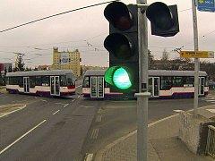 Dopravní komplikace na nové tramvajové trati při křížení ulic Švýcarské nábřeží a Velomoravská. Tramvajová souprava je v křižovatce a na semaforu je zelená.