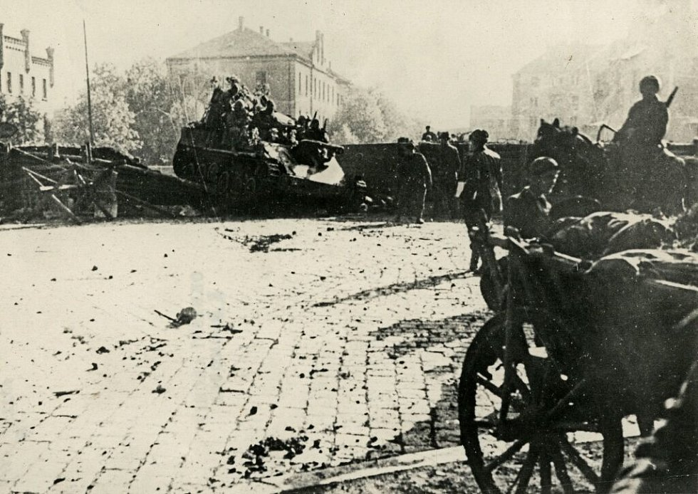 Sovětské samohybné dělo přejíždí přes barikádu v Komenského ulici