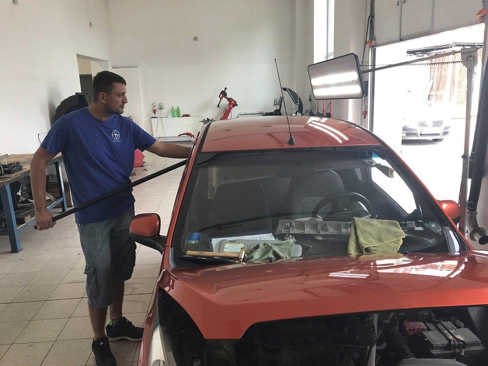 Na opravy karoserií poškozených krupobitím nasadily firmy do Olomouce posily. Motoristům pomáhá například Doktor Důlek a jeho mezinárodní tým. Využívá několik technologických postupů. Na snímku vytlačovací metoda.