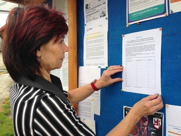 Pracovnice obecního úřadu Helena Petrová vyvěšuje na úřední desku umístního obchodu petici, kterou obec bojuje proti již neúnosné dopravní situaci a uspíšení výstavby R 55Olomouc – Kokory zahrnující obchvat Krčmaně.