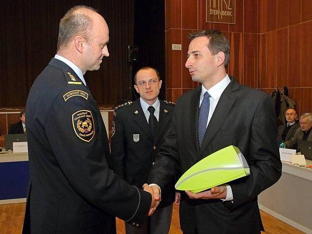 Starosta Stanislav Orság předává defibrilátor šternberským hasičům