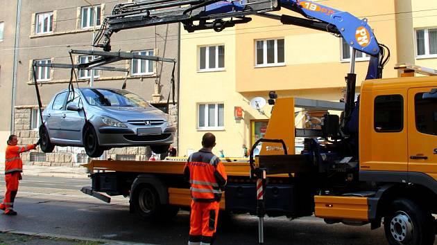Olomoucký půlmaraton vytlačil auta z trasy závodu. Některá museli organizátoři nechat odtáhnout. Řidič auta na snímku zaparkovaného na Masarykově třídě se ovšem pro svůj vůz během jeho nakládání stihl vrátit a nakonec s ním odjel.