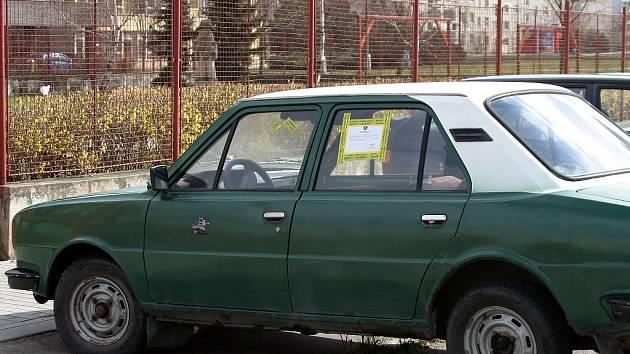 Vysloužilý vůz odstavený na ulici.