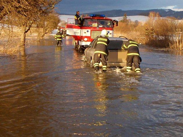 Hasiči vyprošťují auto, které uvízlo na zatopené silnici mezi Dolní Libinou a Novou Hradečnou