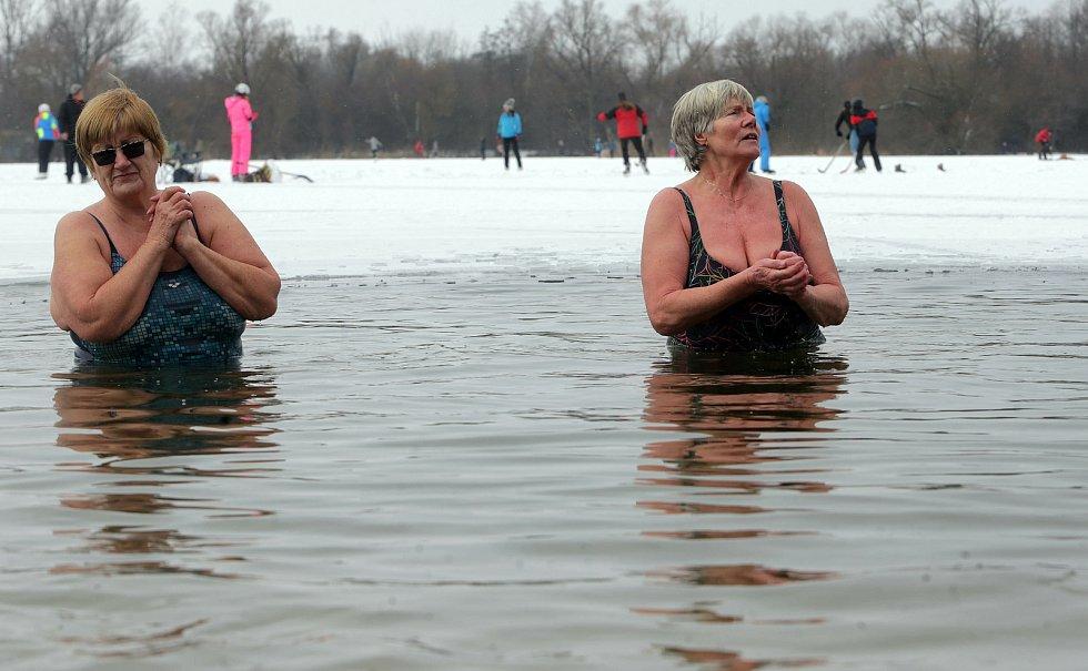Někdo brusle, někdo plavky. Zamrzlé přírodní koupaliště Poděbrady v sobotu 13.2.2021. Množství bruslařů doplňovali otužilci.