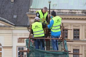 Měděnou korouhev a báň centrální věžičky umístěné na budově olomoucké radnice, které ve středu ze střechy sundali pracovníci odborné firmy, teď čekají opravy. Na své místo se vrátí v následujících měsících.Autor: Eva Minárová