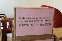Krabice s ochrannými pomůckami polepené česko-čínským nápisem.
