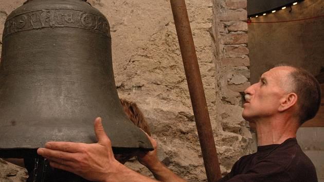 Pracovníci Arcidiecézního muzea v Olomouci zavěšují nejstarší zvon pocházející z českých zemí.