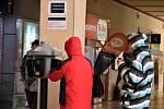 Lidé ve vestibulu hlavního nádraží v Olomouci využívají stojany s dezinfekcí, 23. 3. 2020